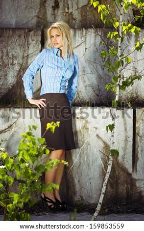 Beautiful blonde woman standing by a stone wall - stock photo