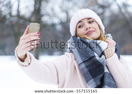 Beautiful blonde woman taking a selfie in winter holidays on the snow