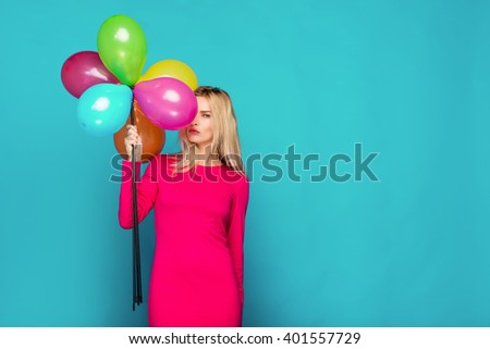 beautiful blonde woman very energetic, smiling and holding some colored balloons on blue background - stock photo