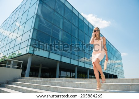 Beautiful, blonde woman walking downstairs while talking on cell phone - stock photo