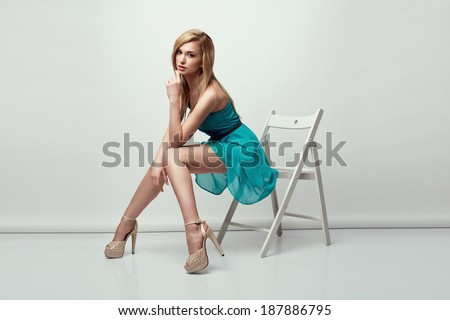 Beautiful blonde woman wearing a blue dress and high heels, sitting on a chair. Studio shot.  - stock photo