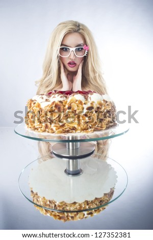 Beautiful blonde woman with a cake. Sweet sexy lady with glasses - stock photo