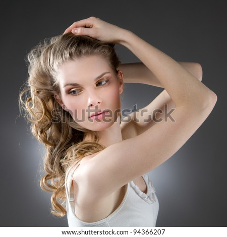 Beautiful blonde woman with arms raised, looking sideways - stock photo