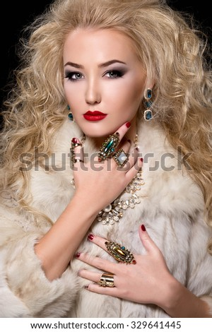 Beautiful blonde woman with curly hairstyle and bright makeup, perfect skin, cosmetology. Sexy vogue woman in fur and jewelry - stock photo