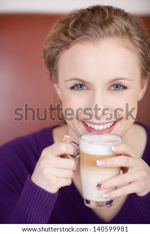 beautiful blonde woman with glass of latte macciato sitting in a caf�© - stock photo