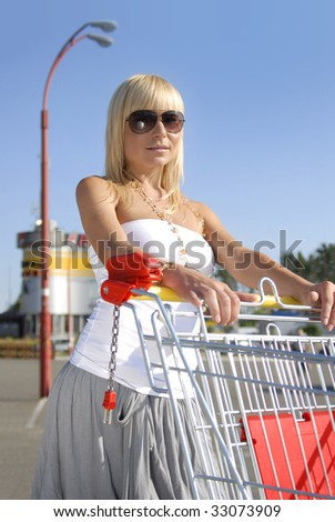 beautiful blonde woman with handcart near a supermarket