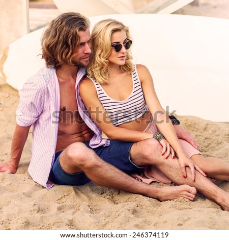 Beautiful blonde woman  with  her handsome  guy  , wearing stylish sunglasses  posing on the tropical summer beach . Warm sunny colors and retro filter . - stock photo