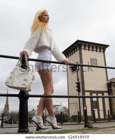 Beautiful blonde woman with long golden hair standing next to railings - stock photo