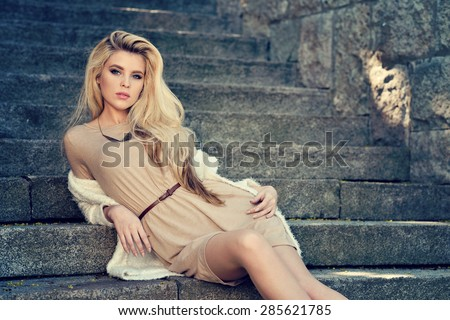Beautiful blonde woman with long hair. Girl in dress outdoors. Pretty lady on beauty background. Female portrait of sexy fashion model - stock photo