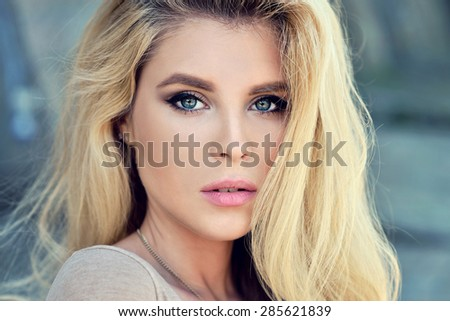 Beautiful blonde woman with long hair. Girl in dress outdoors. Pretty lady on beauty background. Female portrait of sexy fashion model