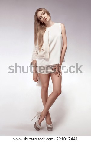beautiful blonde woman with long legs on white background - stock photo