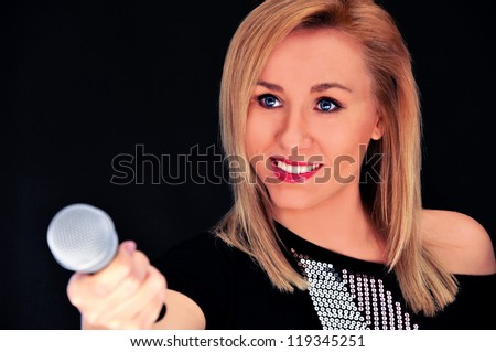 Beautiful blonde woman with microphone on black background