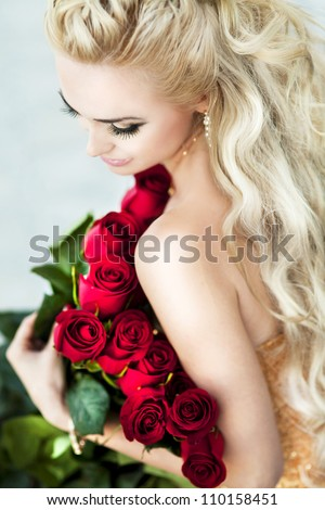 Beautiful blonde woman with red roses and long curly blond hair . Rich alluring girl in love dreaming and holding bouquet. lovely young lady with fresh flowers near the pool outdoor. series - stock photo