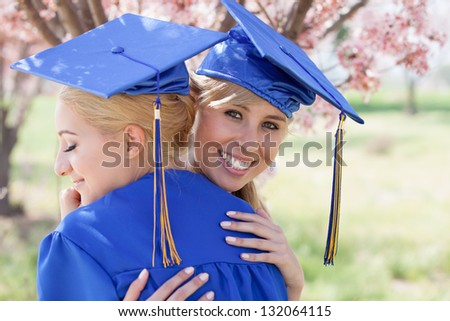 Beautiful Blonde women in blue gowns embracing celebrating their graduation - stock photo