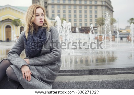 Beautiful blonde young caucasian woman in grey coat and scarf walking in european city on a cold rainy cloudy day, a bit sad and thoughtful. copy space - stock photo