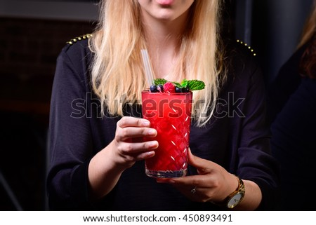 beautiful blonde young girl lady holding drink cocktail red fruit strawberry mint blueberry frozen daiquiri Close-up of glamorous  in the night club dark background - stock photo