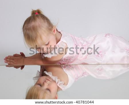 Beautiful blonde young girl looking in the mirror, studio shot - stock photo
