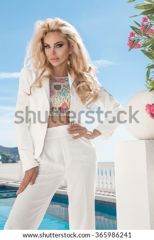 Beautiful blonde young sexy model with long hair standing at exclusive pool with in elegant suit, jacket with crystals in the background of lush vegetation, sea, blue sky in Santorini island, spain - stock photo