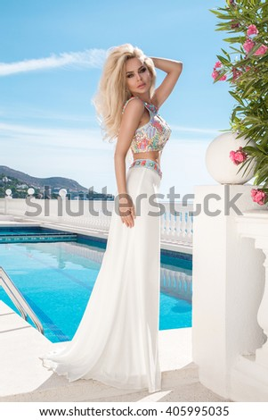 Beautiful blonde young sexy model with long hair standing at exclusive pool with in long dress with  crystals in the background of lush vegetation, sea, blue sky and ships in Santorini island, spain - stock photo