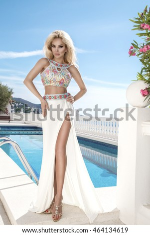 Beautiful blonde young sexy model with long hair standing at exclusive pool with in long dress with  crystals in the background of lush vegetation, sea, blue sky and ships in Santorini island, spain