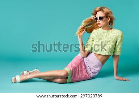 Beautiful blonde young woman in nice clothes, round white sunglasses, high heels sandals. Fashion Photo - stock photo