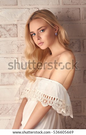 beautiful blonde young woman in white dress stay over bricks wall at home.beauty lifestyle photo