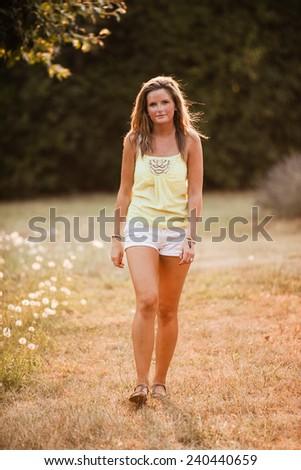 Beautiful Blonde Young Woman walking in meadow closer - stock photo