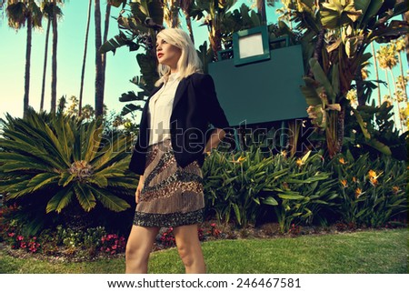 Beautiful blonde young woman wearing fashionable clothes, black cardigan walking on the street with palm trees. Fashion photo  - stock photo