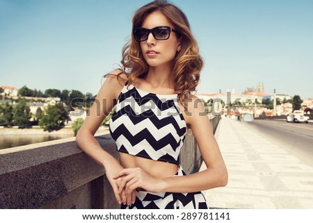 Beautiful blonde young woman wearing fashionable clothes, handbag, sunglasses posing in the city. Fashion photo