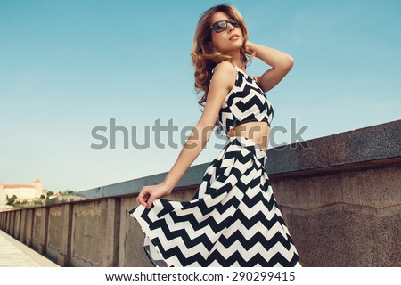 Beautiful blonde young woman wearing fashionable clothes, skirt, handbag, sunglasses posing in the city. Fashion photo - stock photo
