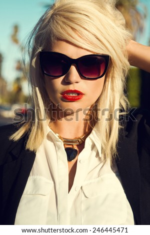 Beautiful blonde young woman wearing sunglasses, black cardigan, red lips. Fashion photo