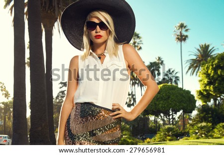 Beautiful blonde young woman wearing sunglasses, glitter skirt, wedges, summer hat, red lips walking on the street, palm trees. Fashion photo, California - stock photo