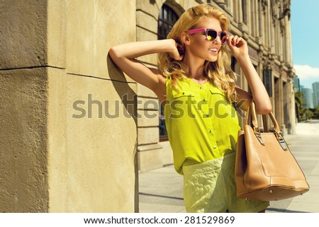 Beautiful blonde young woman wearing sunglasses, shorts, green top and handbag, standing on the street