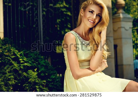Beautiful blonde young woman wearing yellow summer dress, posing in the parc - stock photo