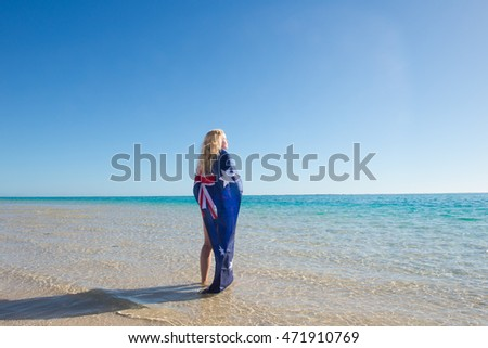 Beautiful blonde young woman with Australian flag relaxed in water at tropical beach, turquoise ocean, summer sunny blue sky, copy space.