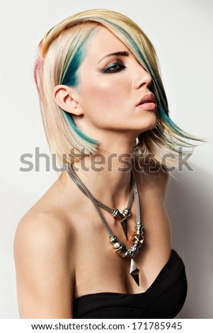 beautiful blonde young woman with fancy coloured hair; portrait of a fashion model with dyed hair - stock photo