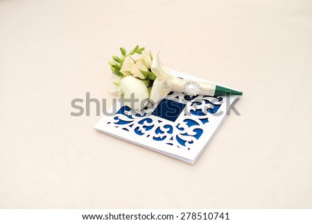 Beautiful blue and white wedding invitations and boutonniere lying at the light table top on celebration background copyspace closeup, horizontal picture - stock photo