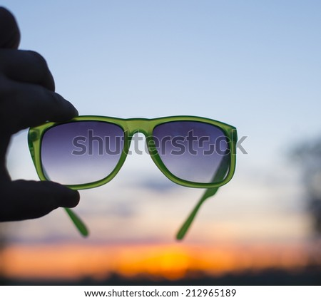Beautiful blue and yellow sunset cloudy sky through stylish accessory  Silhouette Man's hand holding sunglasses Empty copy space for inscription - stock photo