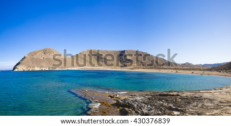Beautiful blue bay and mountains against of bright clear sky, in the playazo of Rodalquilar in Spain natural park of Cabo de Gata, nijar, andalucia, spain - stock photo