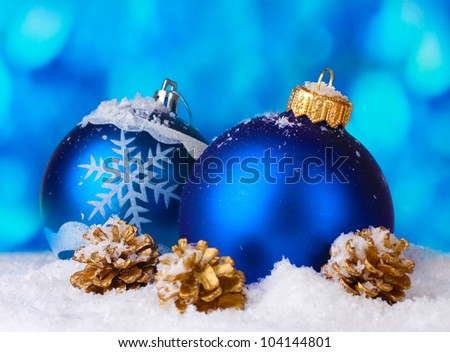 beautiful blue Christmas balls and cones in snow on blue background - stock photo