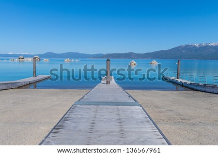 Beautiful blue clear water pier on the shore of the lake Tahoe - stock photo