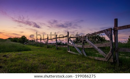 Beautiful blue-colored landscape, old wooden fence in the foreground - stock photo