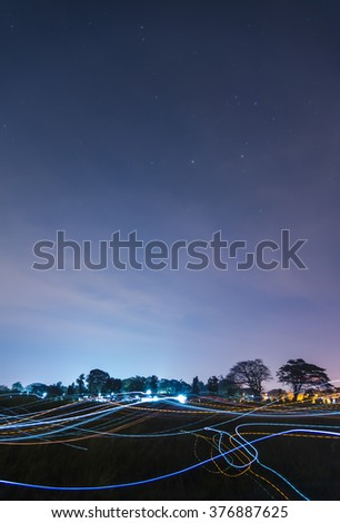 Beautiful Blue dark night sky and stars above field of grass and colorful of light - stock photo