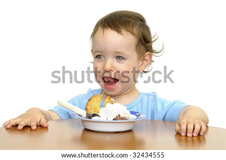 Beautiful blue eyed baby eating icecream with a spoon isolated in white
