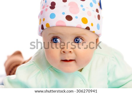 Beautiful blue-eyed baby in the cap. Close-up. Studio photo - stock photo