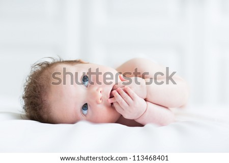 Beautiful blue eyed baby with curly hair sucking on both hands - stock photo