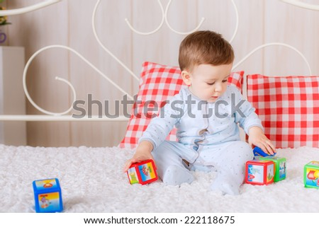 beautiful blue-eyed boy in pajamas on the bed in the nursery - stock photo