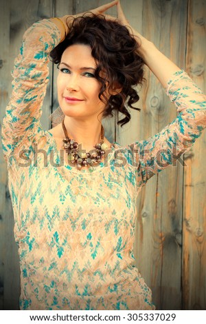 Beautiful blue-eyed brunette on old wooden background. instagram image filter retro style - stock photo