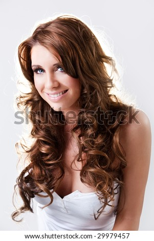 Beautiful blue eyed brunette with curly hair happily smiling - stock photo