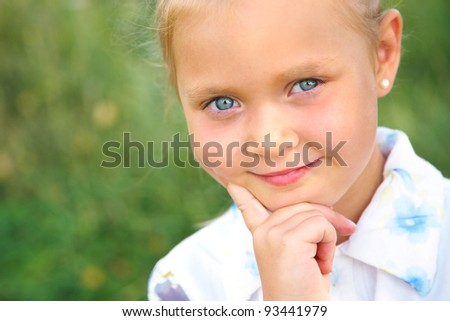 Beautiful blue-eyed little girl smiling sweetly at the camera - stock photo